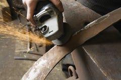 Herrero Using Angle Grinder en el borde de la herramienta del metal imagen de archivo