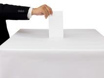 Herrhand, die einen Abstimmungsstimmzettel in Schlitz des weißen Kastens einsetzt Stockbild