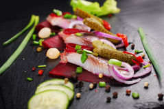 Herring appetizer with beets and gherkin on black slate board Royalty Free Stock Photos