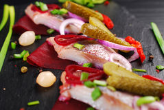 Herring appetizer with beets and gherkin on black slate board Stock Image