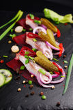 Herring appetizer with beets and gherkin on black slate board Royalty Free Stock Photography