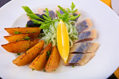 Herring with baked potato on plate Royalty Free Stock Image