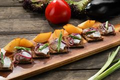 Herring with baked potatoes and onions on tray on wooden background stock photography