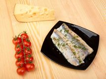 Herring on black plate Stock Photos