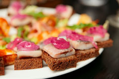 Herring canapes in plate, close-up Royalty Free Stock Photography