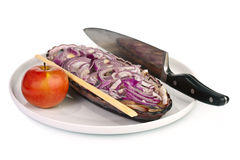 Herring dish. Sliced herring served with fresh red onion, apple, knife and chopsticks Royalty Free Stock Images