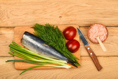 Herring double fillet with vegetables on wooden table Royalty Free Stock Photo