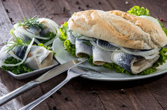 Herring Filet on a baguette (against wood) Stock Photography