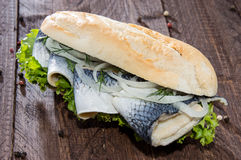 Herring Filet on a baguette (against wood) Royalty Free Stock Images