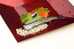 Dutch new herring. Herring fillet with national symbols of the Netherlands: a Dutch flag and orange flag, chopped onions, and lettuce on a red plate Stock Photo