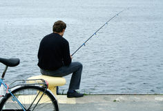 Herring fishing. A male sitting at ease on a mooring with his bike behind him, waiting for herring to bite Royalty Free Stock Image