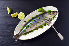 Herring with green onion. On a black wooden table Stock Photos