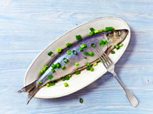 Herring with green onion. On a wooden table Royalty Free Stock Photography