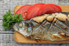 Herring, grilled, sliced tomato and parsley on a cutting Boards Royalty Free Stock Image