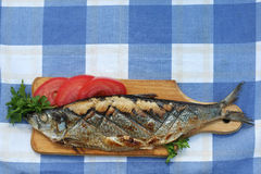 Herring, grilled, sliced tomato and parsley on a cutting Boards Stock Image