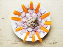 Herring matjes with onion circle and carrot slice in circle Royalty Free Stock Photos