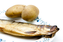Herring with peeling potatoes. On plate and on white background Royalty Free Stock Images