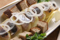 Herring with potatoes. Pieces of boiled potatoes with herring and onion Royalty Free Stock Images