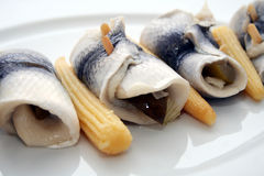 Herring rolls. A plate of herring rolls decorated with little corns royalty free stock image