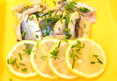 Herring salad with lemon on a yellow background Stock Photos