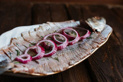 Herring with sliced onions. Herring in oil with sliced onion on a brown table Stock Photo