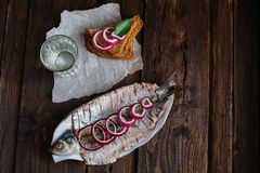 Herring with sliced onions. Herring in oil with sliced onion on a brown table with vodka and sandwich Stock Photo