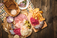Herring and snack on wooden background. Snack for vodka, bacon pickles, herring and sprat. Wooden board with snacks Royalty Free Stock Photo