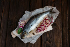 Herring and spices. Herring with onion and spices on a brown table Stock Image