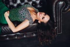 Herrlich und Schönheit im grünen Kleid, das auf schwarzem ledernem Sofa liegt lizenzfreie stockfotografie