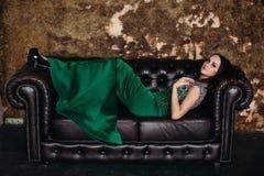 Herrlich und Schönheit im grünen Kleid, das auf schwarzem ledernem Sofa liegt stockfoto