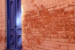 Herrliche alte Backsteinmauer mit Schalenfarbe und hellen blauen Türen Stockfotos