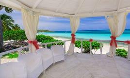Herrliche Ansicht vom Innere des verzierten Heiratsgazebo gegen Hintergrund des ruhigen Ozeanstrandes und des blauen Himmels Stockfotografie