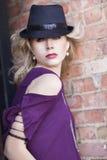Herrliche blonde behaarte Frau, die gegen Wand mit schwarzem Hut und purpurroter Bluse steht Lizenzfreie Stockfotos
