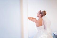 Herrliche blonde Braut auf einem weißen Hochzeitsinnenraum mit Kopienraum Stockbild