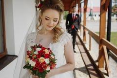 Herrliche blonde Braut, die mit Blumenstrauß, glückliche Jungvermähltenfrau aufwirft Stockfoto