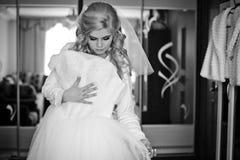 Herrliche blonde Braut, die mit elegantem Hochzeitskleid im Hotel aufwirft Lizenzfreie Stockfotos