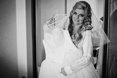 Herrliche blonde Braut, die mit elegantem Hochzeitskleid im Hotel aufwirft Stockbilder