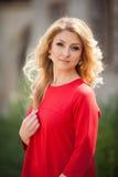 Herrliche blonde Braut im roten Kleid, das draußen aufwirft Stockfotografie