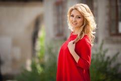 Herrliche blonde Braut im roten Kleid, das draußen aufwirft Lizenzfreie Stockbilder