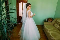 Herrliche blonde Braut im weißen Kleid, das als Vorbereitung auf die Hochzeitszeremonie im Raum aufwirft Stockfoto