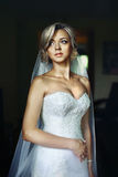 Herrliche blonde Braut im weißen Kleid, das im Hotelzimmer aufwirft Lizenzfreie Stockfotografie