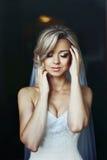 Herrliche blonde Braut im weißen Kleid, das im Hotelzimmer aufwirft Stockbilder