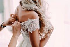 Herrliche, blonde Braut im weißen Luxuskleid wird zur Heirat fertig Morgenvorbereitungen Frau, die auf Kleid sich setzt Stockfotos
