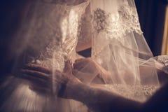 Herrliche, blonde Braut im wei?en Luxuskleid wird zur Heirat fertig Morgenvorbereitungen Frau, die auf Kleid sich setzt lizenzfreie stockfotografie