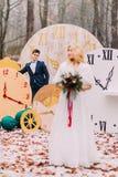 Herrliche blonde Braut mit Blumenstrauß im Herbstwaldschattenbild des Bräutigams auf Hintergrund Stockbild