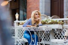 Herrliche blonde Dame, die an etwas bei der Entspannung in der Kaffeestube in der Frischluft denkt Stockbilder