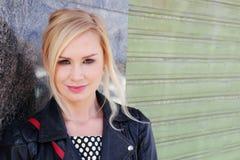 Herrliche blonde Frau, die auf der Wand sich lehnt Stockbilder