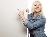 Herrliche blonde Frau, die auf ein Brett bei der Stellung gegen zeigt Lizenzfreies Stockfoto