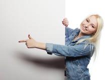Herrliche blonde Frau, die auf ein Brett bei der Stellung gegen zeigt Lizenzfreie Stockbilder