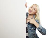 Herrliche blonde Frau, die auf ein Brett bei der Stellung gegen zeigt Stockbild